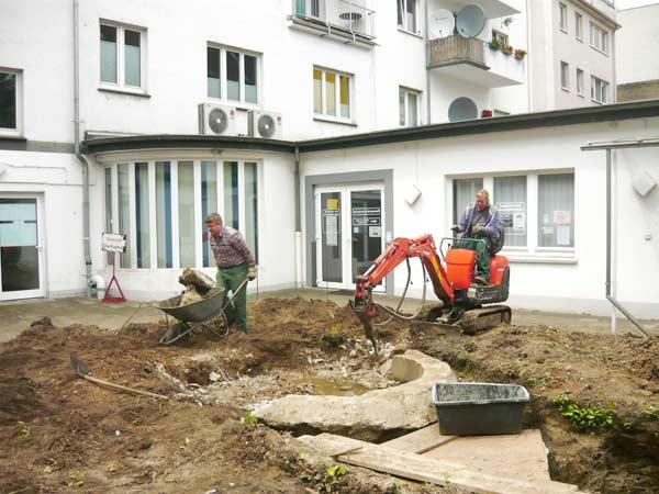 Bei der Umgestaltung des Innenhofes am Ostwall 85 vor der Geschäftsstelle der Krefelder Familienhilfe e.V. stellte sich ein alter massiver Betonspringbrunnen in den Weg. Dank Bagger mit Stemmhammer ist selbst Schwerstarbeit keine reine Männersache mehr.