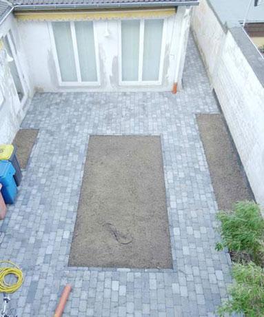 Nach dem Verlegen des Betonpflasters mit drei verschiedenen Längenmaßen und gebrochener Kante, erhält der Hof seine neue Struktur.